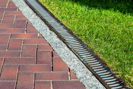 Drainage system with iron mesh along the pedestrian sidewalk with red tiles and green lawn, close-up of iron rainfall. 스톡 콘텐츠