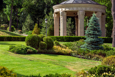 Stone arbor with columns in the park with landscape design and green summer plants in the foreground meadow with lawn and bushes, in the background deciduous trees.