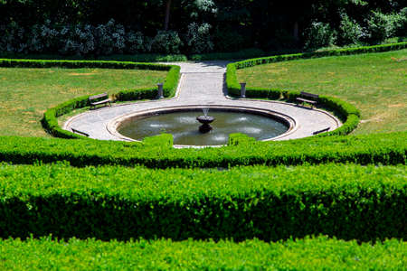 a stone round fountain with water surrounded by a walkway of tiles with wooden benches and a hedge of evergreen boxwood bushes on a sunny summer day. Banque d'images