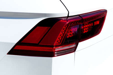 rear headlight white car close-up stop signal with turn signals.