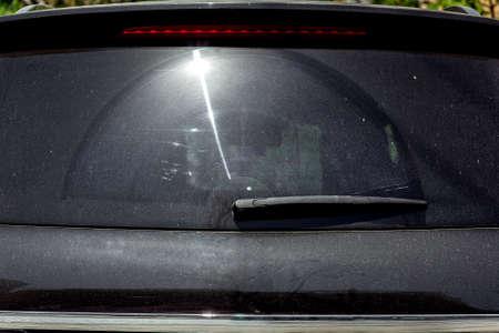 Achterruit van een zwarte vuile auto bedekt met stof met een zonnevlam. Stockfoto