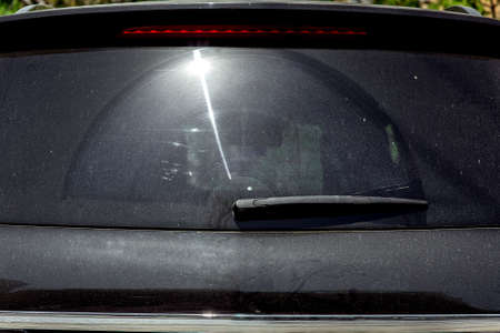 Rear window of a black dirty car covered in dust with a sun flare. Foto de archivo