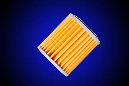 Car filter orange paper for automatic transmission gearbox variator, isolated spare part on a gradient blue to black background with copy space.