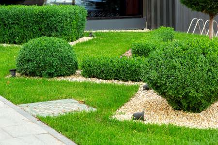 前景に小石と箱木の茂みを持つマルチングマンホール、詳細クローズアップで造園。