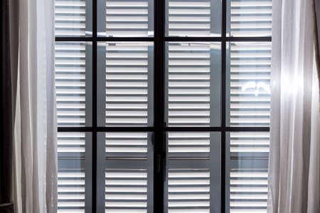 graue Holzfensterläden schützen den Raum vor übermäßiger Sonneneinstrahlung, ein Fenster mit geschlossenen Fensterläden und offenen Vorhängen aus weißen Textilien.