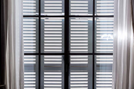 gray wooden window shutters protect the room from excessive sunlight, a window with closed shutters and open curtains of white textiles.