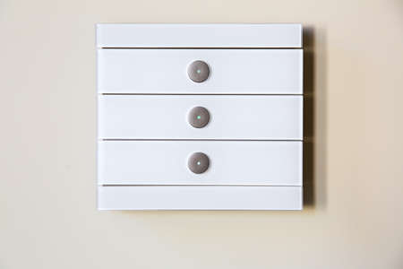 A modern white glass touch sensitive multifunctional light switch with indicators instal on a beige wall close up. Stock Photo