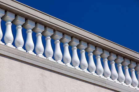 white stone balustrades over the wall architecture of the Baroque against the blue sky on a sunny day.