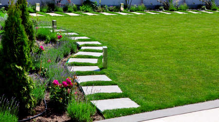 backyard garden with a flower bed with roses and lavender with a path of marble tiles on the meadow with a green lawn on a sunny day.