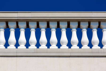 Baroque architecture details of stone railings with white balustrades close up against a blue sky.