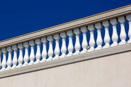 white balustrades with stone railing in gray against a blue sky, details of architecture in the Italian style.