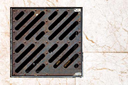 storm shower iron grate on a pedestrian pavement of marble top view close up. Reklamní fotografie