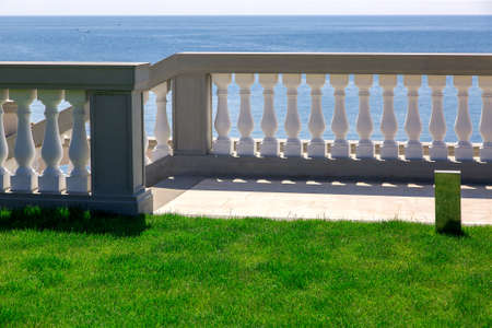 white balustrades with gray railings and a marble walkway with a green lawn, descent to the sea of an elite mansion.