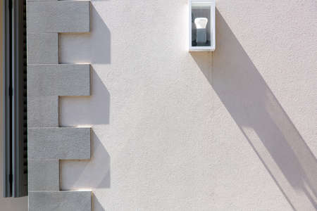 the stone wall is light beige in color with a molding on the corner of the building and a white wall lamp of square shape with a light bulb. Reklamní fotografie