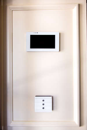 Smart home control system, Controls the functionality of the system, a touchscreen tablet with a screen and a white touchscreen switch buttons mounted on a beige wall.