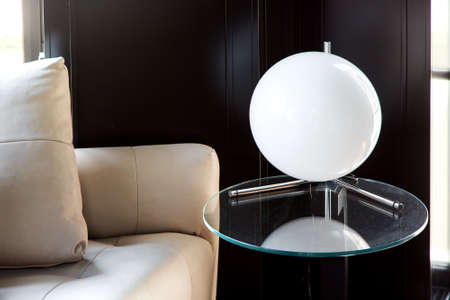 table lamp white ball on a glass round table against a black wooden wall and leather sofa, closeup of an interior lantern.