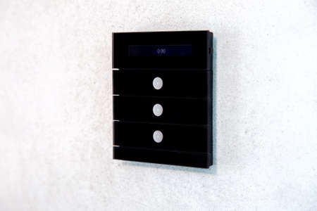 multi function light switch for controlling functions of a smart home with three buttons and a digital display in black on a light wall side view.