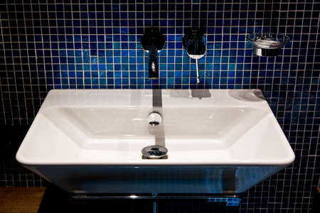 white ceramic washbasin with an iron tap in the bathroom with a wall in blue mosaic.