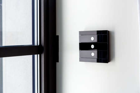touch glass light switch of black color on a white wall near the window, close-up of the smart home control with 3 buttons. Reklamní fotografie