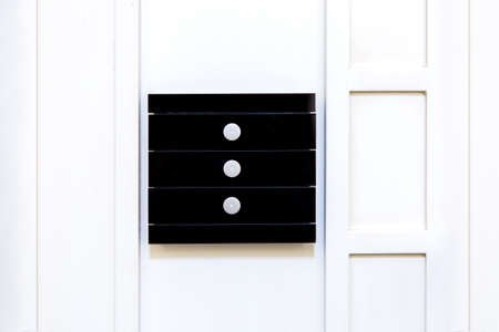 Black glass multifunctional light switch with three touch buttons mounted on a white wooden wall, close up of the element smart home control. Reklamní fotografie