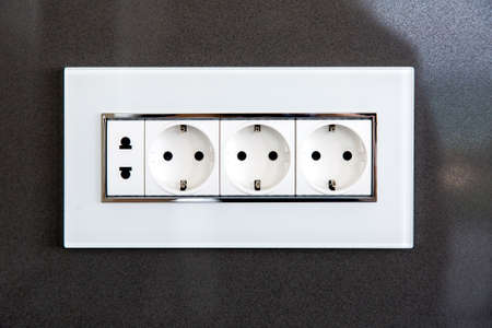 socket with plugs for standard type A plug and standard type F plug in white plastic case on a dark gray glossy stone wall. Reklamní fotografie