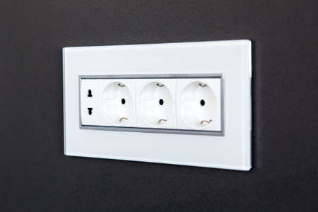 socket with plugs for standard type A plug and standard type F plug in white plastic case on a dark gray stone wall, close up side view.