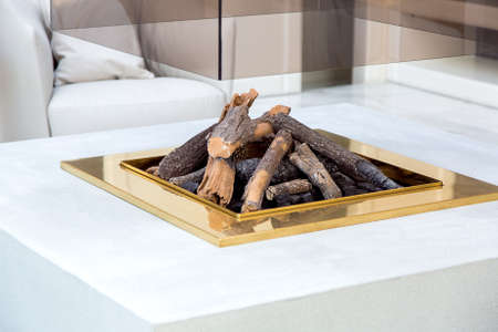 open fireplace in the center of the living room with a stone worktop and a glass chimney body, close up of the fireplace with firewood and a gold frame.