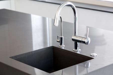 Küchenspüle aus dunkelgrauem Stein mit verchromtem Wasserhahn in einer sauberen Küche mit glänzender Arbeitsfläche, Nahaufnahme des Wasserhahns.
