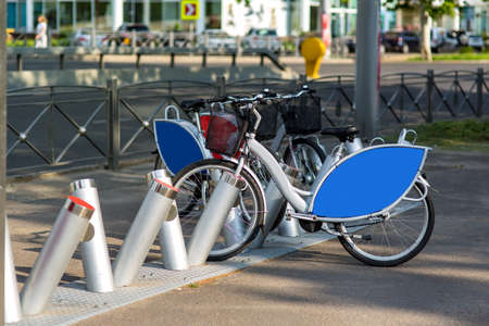 bicycle rental in a city park on the background of the road, rental bike gray with blue advertising space.