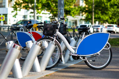bike rental in a city park on the background of the road with traffic jam,  rental bike gray with blue advertising space.