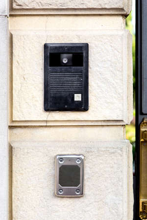 An intercom with a call button and a camera with a microphone on a stone wall with a rusticate on the bottom of the card reader for access. Standard-Bild - 129229405