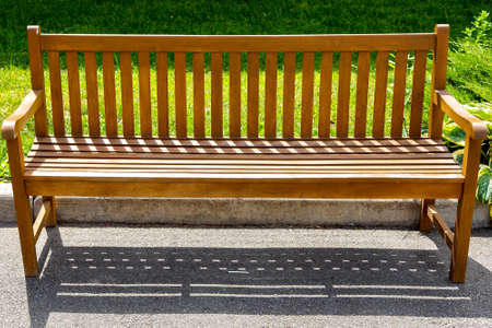 a wooden brown bench made of boards stands on an asphalt pavement near the curb with a green lawn in the park. Reklamní fotografie