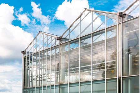 greenhouse made of transparent glass construction exterior against the sky.