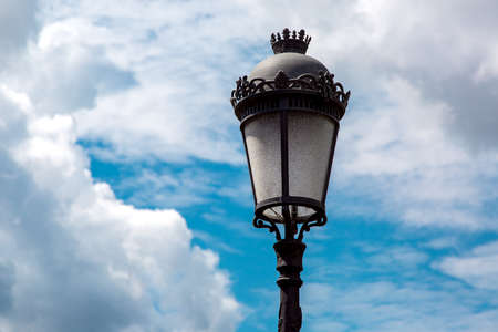 black iron street lamp with a pattern and a glass shade against the sky with clouds on a sunny day.