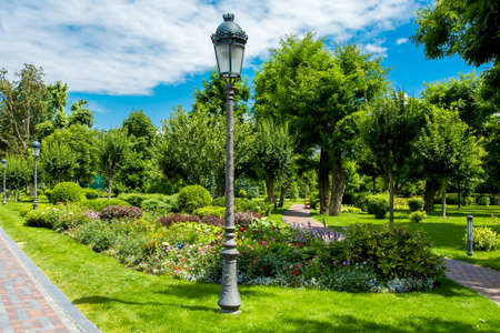 the park has walkways and growing plants around flower beds and green bushes with trees, iron lampposts with retro street lamps are installed on green lawns.