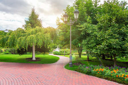 pedestrian sidewalk in a park with green plants and an iron retro lantern, trees and flowers in flower beds with sun flare.
