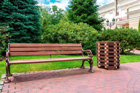 a bench with iron forged legs and brown wooden seats with a litter bin from the boards in the backyard in the garden with green plants in the background the facade of the building with a lantern.
