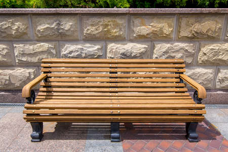 wooden bench with iron legs on the tile and on the stone wall with rustic elements.
