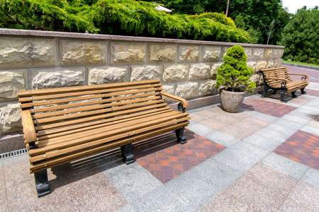wooden benches on a pedestrian sidewalk made of tiles near a stone wall with a rustic and stone flowerpot for plants in a park with pine trees and thuja. Standard-Bild - 129227147