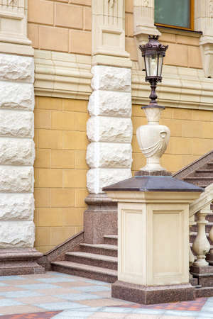 the facade of the building in retro style is decorated with stone with a stone staircase with a pedestal and a vase on which a street lamp is installed.