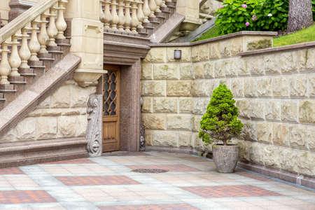 building facade exterior with architectural elements of stone decor style with entrance door. Foto de archivo - 129227150