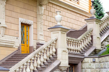 the facade of the building with a granite staircase and stone railings with balustrades with stone vases on pedestals and other architectural details of the structure. Standard-Bild - 129227151
