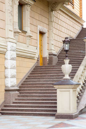 architectural stone staircase near the facade of the building with railings and balustrades with a pedestal for a stone vase with an iron street lamp in retro style. Standard-Bild - 129227041