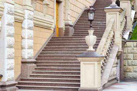 architectural stone staircase with railings and balustrades with a pedestal for a stone vase with an iron street lamp in retro style.