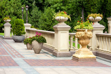 stone flowerpots at the railing with balustrades on the backyard terrace with paving tiles and a park of trees in the background. Stockfoto - 129227072