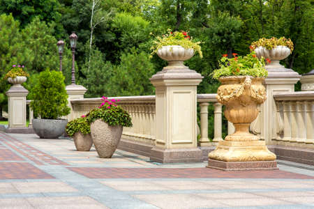 stone flowerpots at the railing with balustrades on the terrace with paving tiles and a garden of trees in the background. Reklamní fotografie
