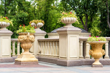 stone flowerpots at the railing with balustrades on the terrace and a garden of trees in the background.