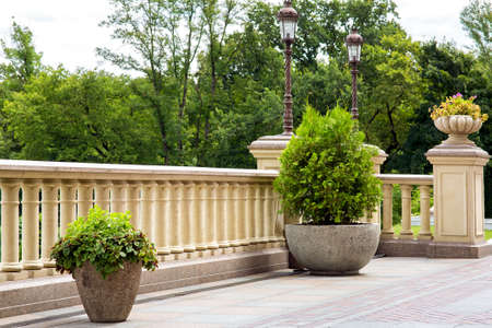 stone flowerpot with thuja near the railing with a balustrade and a stone flowerpot on a pedestal and posts with lanterns in retro style in the background tree branches and a cloudy sky.