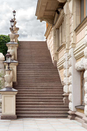 granite staircase on the side of the facade of the building made of stone architectural elements and pedestals with stone vases. Standard-Bild - 129227067