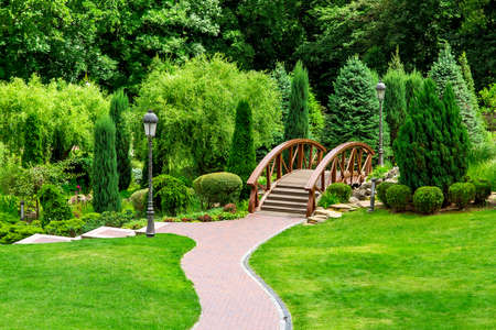 Landscaping of a park in the backyard with a path for walks through the garden through a wooden decorative bridge to bushes and trees.